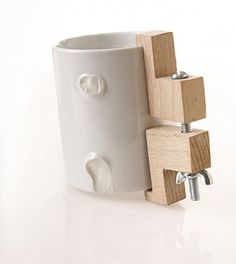 Handle with Care (Yuval Tal, 2006): a collection of ceramic cups in their second life by metal and wood clamps.