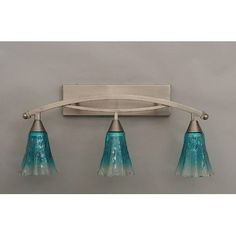 "Bow 3 Light Bath Vanity Light Finish: Brushed Nickel, Shade: 5.5"" Teal Crystal Glass by Toltec Lighting. $297.00. 173-BN-725 Finish: Brushed Nickel, Shade: 5.5"" Teal Crystal Glass Features: -Bath vanity light. -Bow collection. -Number of lights : 3. -Material : Glass. -Manufacturer provide one year warranty. Specifications: -Backplate dimensions: 4.25"" H x 16"" W x 1"" D. -Overall dimensions: 11.25"" H x 10"" W x 29"" D."