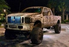 Muddy white lifted Ford truck Mudder