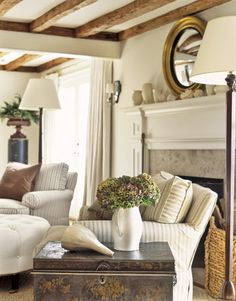wood beams, soft colors... LOVE the circle mirror above the mantle!