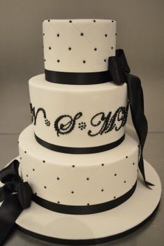 The lettering is effective. Simplistic monogram black and white round wedding cake