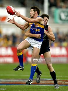 Ben Cousins #9 for the Eagles is tackled by Jordon Bannister #31 for the Blues during the round five AFL match between the Carlton Blues and the West Coast Eagles at Optus Oval April 24, 2004 in Melbourne, Australia.