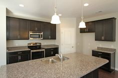 The rich dark stained Aristokraft cabinets go well with neutral paint color and the clean look of these GE stainless appliances. View the Allendale floor plan at http://www.hunterquinnhomes.com/Home-Plans/Allendale.aspx
