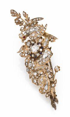 BROCHE TREMBLEUSE <br>en fleur d'argent doré et d'or jaune, les feuilles et les pétales sertis de diamants taillés en rose et de diamants table, le pistil orné de diamants et rehaussé d'émail bleu, animée d'un oiseau couronné, le corps serti de diamants tables et de roses. <br>Époque XIXe siècle. <br>Dimensions : 9,4 x 3,5 cm environ. <br>Poids : 27,1 g (9K, petite réparation). <br>A 19th century diamond, enamel, silver and 9K gold brooch.
