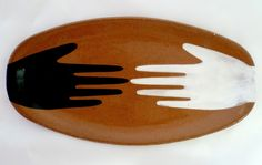 Sharon Muir; Hand hand. Long shallow decorative sandwitch plate hand painted with a double hand pattern in black and white. The 'Mano el Mano' dish is hand formed from from mid fire red clay and each one is individually painted.The Mano pattern was inspired by Mexican icons and the work of Spanish artist Antoni Tapies.Food safe, hand wash only.28cm L x 14.5cm W x 2cm H