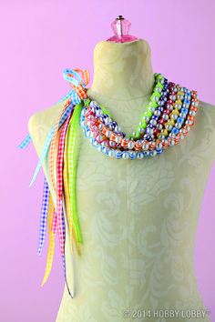 Add a pop of color to any outfit with this DIY necklace! Use a beading needle and beading thread to stitch faux pearls onto gingham ribbon. Push the needle through the ribbon, through a bead, repeating until you've reached the desired length. Ready to wear!