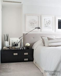 modern, contemporary bedroom design with white paint wall color, gray tufted headboard, white bedding, striped gray & white throw pillows, glossy black lacquer modern nightstand chest, chrome pharmacy lamp and trio of floral art.white gray black bedroom colors.