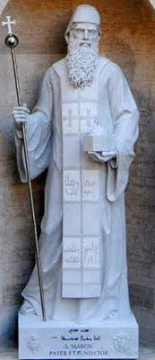 Sculpture of Saint Maron at the Saint Peter's Basilica in the Vatican. At his feet is an inscription in Syriac of the psalms that reads: The righteous will flourish like a palm tree, they will grow like a cedar of Lebanon.