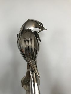 Bird made from upcycled utensils and scrap metal mounted on a reclaimed spindle.