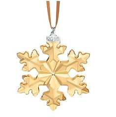 2016 SCS Golden Shadow Annual Edition ornament This latest SCS edition of the Swarovski Christmas Ornament is only available during 2016. It is crafted with beautiful and sparkling golden shadow crystal; a metal dated tag is also included on an elegant brown satin ribbon. Swarovski Christmas Ornament, A.E. 2016 L.E.