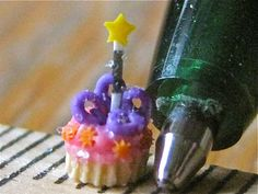 ~*Fairy Cake!*~ next to the tip of a ball point pen from TD bank.    Cupcake & frosting made of polymer clay!  100% polymer clay coated with clear acetate glitter  Amber Dawn  www.Inventivesoul.blogspot.com