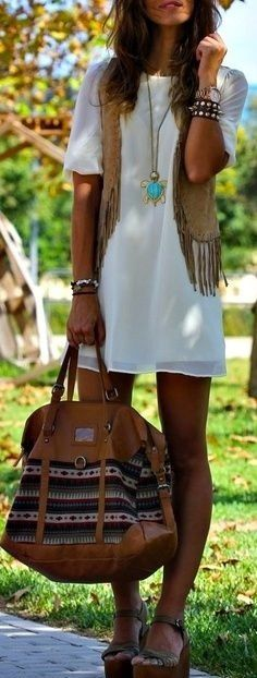 Bohemian white mini dress and modern hippie vest with layered necklaces for a festival gypsy style.
