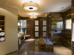 This walk-in shower is tiled in tortoiseshell glass. To enhance the resort-style feel of the bathroom, there is a built-in tiled bench seat, and the shower has no end wall or curb – water simply flows down a linear drain along one wall. The bathroom is lit by two large circular pendant lights.