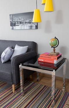 Pendente amarelo na sala de estar deu um toque jovem e moderno para o cantinho da sala. Os livros e o quadro complementam na decor.
