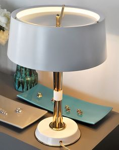 Miles table lamp is a charming decorative element perfect on top of a sideboard, console or a side table. Also a great solution for hotel rooms. Miles table lamp brings back the atmosphere of sophistication inspired by the 50's. Its structure is made in brass and the lampshade in aluminium.
