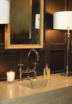 Antique black wall paneling, stone slab sink, gooseneck faucet