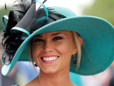A fan smiles as she poses for a photo wearing her derby hat in the infield during the 137th Kentucky Derby at Churchill Downs on May 7, 2011, in Louisville, Ky.