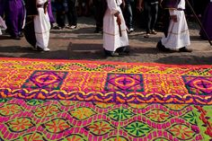 Penitents walk next to a design made with colored wood dust before a Holy Week procession on Good Friday in Antigua Guatemala, Guatemala, on April 6, 2012. The designs are made especially for the processions. (AP Photo/Moises Castillo)