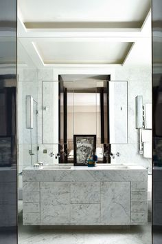A custom-made double vanity, which is crafted of Carrara marble, adds elegance to Paris bathroom in a 19th-century apartment.