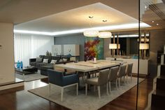 Modern dining room with white table, square dining chairs, white rug and soft design style. By HC Interiores