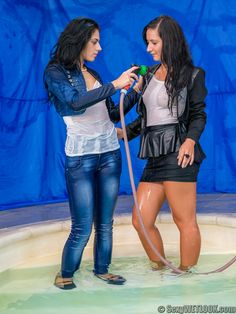 Andreea and Kamilla are together in the pool, one dressed for the office and the other in denim