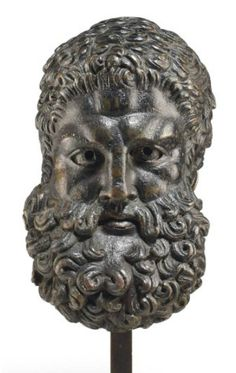 A ROMAN BRONZE HEAD OF HERCULES   CIRCA 1ST CENTURY A.D.   Inspired by the work of Lysippos, the hero depicted with short wavy hair, with a fringe of locks brushed up from the forehead, his forehead creased, the brow knitted, the eyes overlaid in silver, the pupils once further inlaid and now open through to the interior, his lips parted and once overlaid in copper, with a full rounded beard of layered wavy tufts and a full mustache  4 3/8 in. (11.1 cm.) high