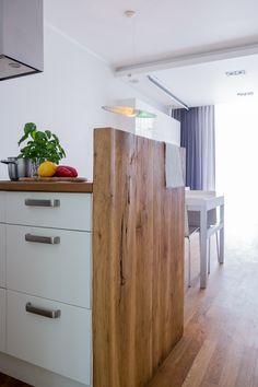 Wyspa kuchenna z dębowym blatem i ścianką z surowego drewna.