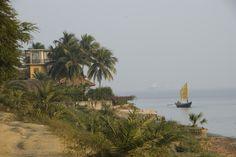 A boat sails along the coast.