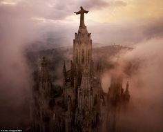 Praying for clear skies: A giant bronze statue of Christ looks down on the fog-shrouded towers of Sagrat Cor Church, high on a hill above Barcelona, Spain