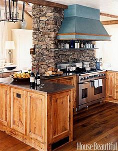 This kitchen might fit right at home in a log cabin. But its style and feel would be great in any open plan. I love the commercial stove and copper hood.