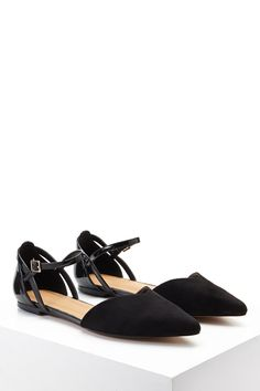 A pair of faux suede flats featuring a pointed toe, faux patent leather back and ankle strap, and a high-polish buckle closure.