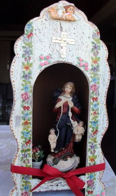 Que coisa mais linda , um lugarzinho bem aconchegante para você colocar o seu Santo preferido. <br>Santo Antonio iria adorar e, garanto, amiga, que se você não tem um amor, ele lhe dará na hora. <br>Oratório em mdf ,com pátina provençal; <br> Ainda esqueci de falar que vai no topo um anjinho em porcelana fria e uma bela cruz de espelho.O lindo vasinho que está no fundo é de cerâmica com flores desidratadas <br>.Decoupage de flores e fita vermelha. <br>Santo não incluido. <br>Acomoda um santo…