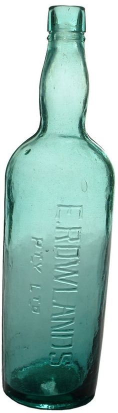 E. Rowlands Pty Ltd. Also embossed Rowlands on the Base. Dark Aqua glass Cordial Bottle. c1910s
