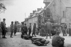 Medical Personnel and French Civilians load casualties onto 2 ½-Ton GMC Trucks for evacuation from 505th (Parachute) Regimental Aid Station #2, Sainte-Mère-Eglise. June, 1944.