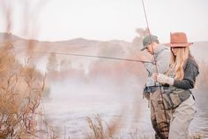 A couple fishing on a riverbank, tying the flies to the hooks for fly fishing. by Mint Images - Photo 155529357 / 500px
