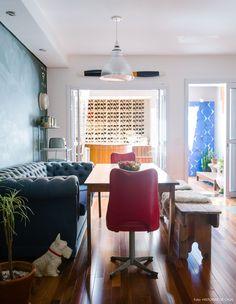 Sala de jantar tem mesa de madeira, sofá chesterfield e cadeiras vintage.
