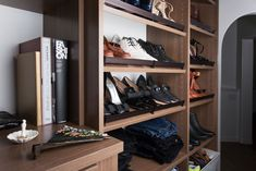Angled shoe shelves in the his-and-hers closet designed for Erica Coffman. #CaliforniaClosets #shoestorage #walkincloset #design