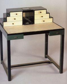 Conçu en 1935, ce bureau-cabinet de Jean-Charles MOREUX est réalisé en bois laqué et gainage de parchemin. Discrète bichromie en noir et blanc et bel agencement de tiroirs en pyramide.