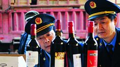Police officers check bottles of confiscated fake wines before destroying them in Xi'an, Shaanxi province. Photo: Reuters