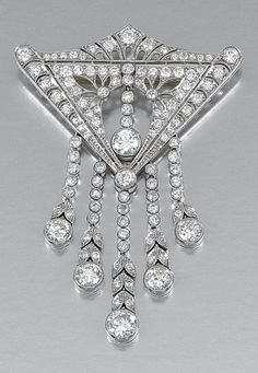DIAMOND BROOCH, CIRCA 1910.  Of stylised pediment design, the central open work motif centring on a pendent line of millegrain-set circular-cut diamonds, suspending a similarly-set tassel embellished with foliate links.