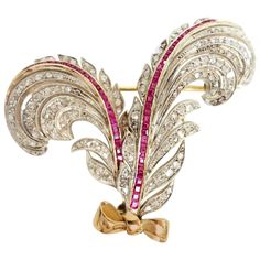 Art Deco Ruby, Diamond, Yellow Gold and Silver Fan Brooch Pin. Gorgeous Art Deco Ruby and Diamond brooch crafted in 18K Yellow Gold and Silver. Featuring a fan/feather design, set with a spray of rose cut diamonds surrounding two ruby set ribbons.
