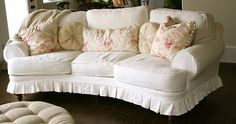 White slipcover sofa, pleated skirt showing some leg, piping added for interest. by Custom Slipcovers by Shelley