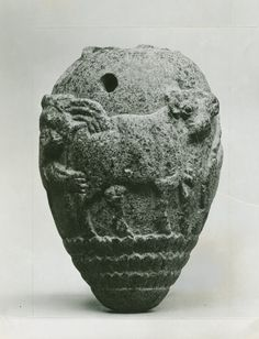 3,300 BCE-3,000 BCE. Uruk Late Period;  Sumerian Culture: Iraq, Syria or Turkey.  Egg shaped carved granite jar with flat base; carved with two lions attacking bulls. Below are 3 registers in a scale pattern. Neck is broken off. The drilled holes indicate that it was likely suspepended.