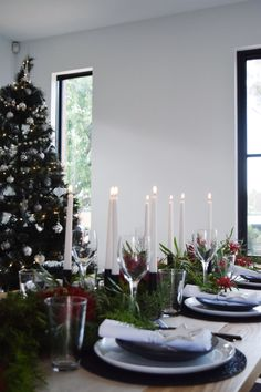 Contemporary Christmas tablescape using matte black plates and candleholders. Floral arrangement is a quick, inexpensive and striking centrepiece.