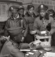 """""""Tuskegee Airmen series. 'Escape kits' (cyanide 'Suicide Rations') being distributed to fighter pilots at air base in Ramitelli, Italy."""" Theodore G. Lumpkin Jr., seated, with (L-R): Joseph L. """"Joe"""" Chineworth, Memphis, Class 44-E; Robert C. Robinson, Asheville, Class 44-G; Driskell B. Ponder, Chicago, 43-I; Robert W. Williams, Ottumwa, Iowa, 44-E. Gelatin silver print by Toni Frissell.  1945"""