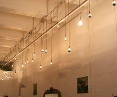 Lighting perpendicular to exposed joists. A messy, more industrial look with the light cables looped around and down from the conduit.