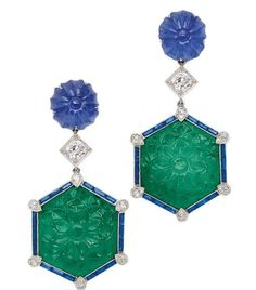 A pair of emerald, sapphire and diamond ear pendants of floral design, each suspending a carved hexagonal emerald plaque framed by channel-set sapphires accented by small round diamonds, topped by an old European-cut diamond to a circular carved sapphire surmount, mounted in platinum