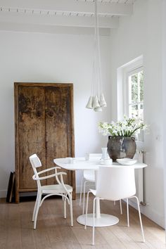 Beautiful balance of old worn wood cabinet with stark white modern table and chairs.
