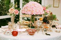 Elegant tea party decorations on a fancy table with large centerpiece of pink roses.