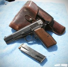 Belgian Browning Hi-Power semi-automatic pistol with magazine and holster.